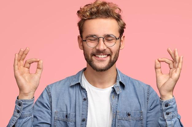 無精ひげで陽気な満足した男性の肖像画、ムドラの看板に立って、目を閉じて、前向きな笑顔を持って、ピンクの壁に屋内で立って、ジーンズのシャツを着ています。人とボディーランゲージの概念 無料写真