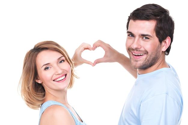 Портрет веселой улыбающейся пары, стоящей вместе, показывает сердце руки - изолированные Бесплатные Фотографии