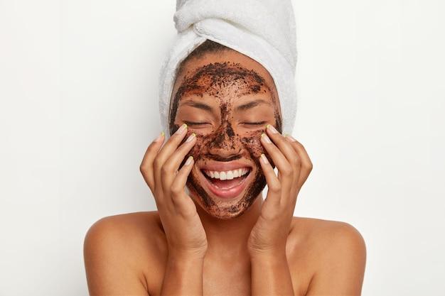 Портрет жизнерадостной улыбающейся темнокожей женщины накладывает маску из натурального кофе, делает круговые движения руками и массирует кожу, стимулирует кровоснабжение лица, носит на голове обернутое полотенце. Бесплатные Фотографии