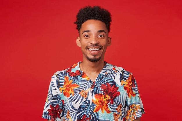 Портрет веселого молодого афроамериканца, одетого в гавайскую рубашку, смотрит в камеру с счастливым выражением лица, стоит на красном фоне и широко улыбается. Бесплатные Фотографии