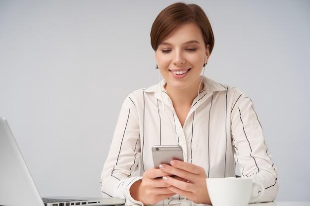 白に座ってメッセージを読んでいる間広く笑顔で携帯電話を上げた手で維持する短い流行のヘアカットと陽気な若い茶色の髪の女性の肖像画 無料写真