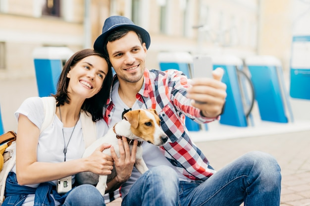 ハンサムな夫に傾いて、selfieのポーズをしながらカメラにうれしそうに笑っている陽気な若い格好良い女性の肖像画。 Premium写真