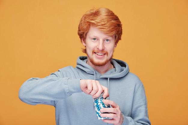 彼の免疫の世話をしながらビタミンボトルを開くパーカーで陽気な若い赤毛の男の肖像画 Premium写真