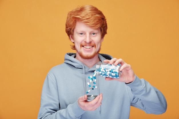 Портрет веселого молодого рыжего мужчины с дрянной усмешкой, сбрасывающего таблетки из бутылки на апельсине Premium Фотографии