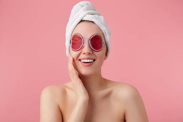 スパ後の陽気な若い女性の肖像画。頭にタオルをかけ、目のマスクを付け、広く笑顔で、とても幸せに感じ、立っています。 無料写真