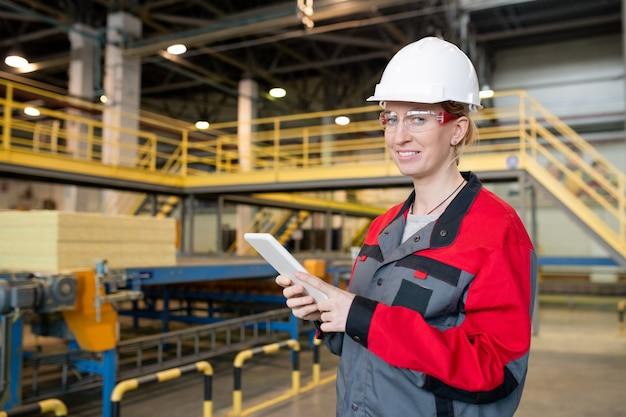 건설 공장에서 태블릿에 데이터를 확인하는 보호 고글과 안전모에 쾌활한 젊은 여자의 초상화 프리미엄 사진