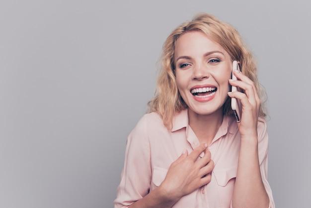 グレーに分離されたスマートフォンで話す陽気な若い女性の肖像画 Premium写真