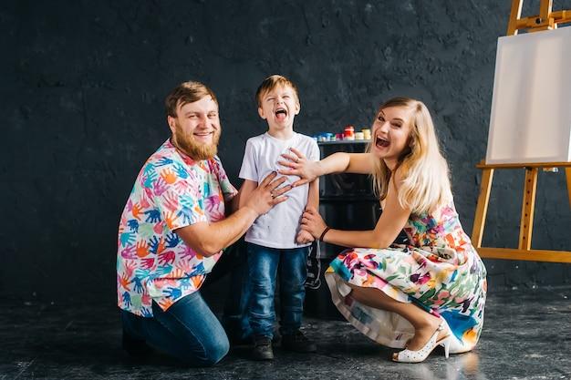 絵を描いて楽しんでいる子供の肖像画。彼らは明るい色で描かれた自分の手を示しています。私たちは家にいて、楽しんで描きます Premium写真