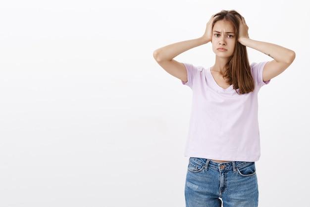 灰色の壁に対して困惑して疲れている頭に手を繋いでいるカジュアルなtシャツで心配してうんざりして問題を抱えた女性の肖像画 無料写真