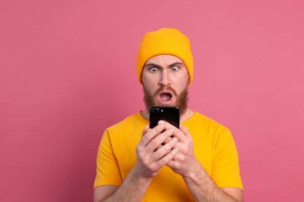 걱정되는 충격을받은 성숙한 수염 난 남성의 초상화는 핑크색에 이상하고 방해 메시지를 읽고 불행한 지주 스마트 폰을 헐떡이며 무료 사진