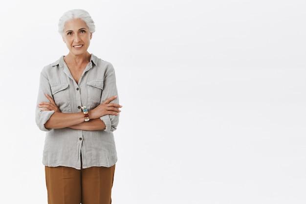 Портрет уверенной в себе очаровательной и харизматичной пожилой женщины из европы в повседневной одежде, скрещивающей руки на теле, улыбаясь уверенным взглядом Бесплатные Фотографии