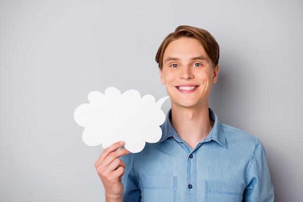 自信を持ってクールなポジティブな女の子の肖像画は、白い紙のカードの泡を保持し、灰色の背景の上に分離された格好良い服を着て彼の視点を共有します Premium写真