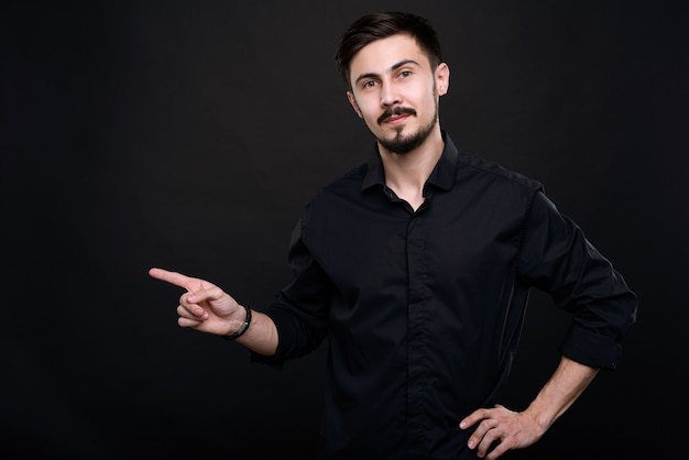 Портрет уверенного менеджера по продажам с усами и бородой, указывая пальцем в сторону, рекомендуя продукт Premium Фотографии