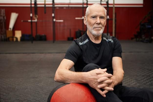 Портрет уверенного в себе кавказского пожилого мужчины с бородой, выбирающего здоровый активный образ жизни, сидя на полу с мячом, отдыхая после интенсивной тренировки в тренажерном зале Бесплатные Фотографии