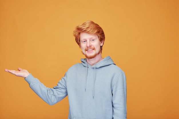 オレンジ色の広告をしながら脇を指しているパーカーの若い赤ひげのブロガーのコンテンツの肖像画 Premium写真