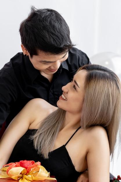 リビングルームでプレゼントを祝うギフトボックスプレゼントを持っているカップルの肖像画 Premium写真