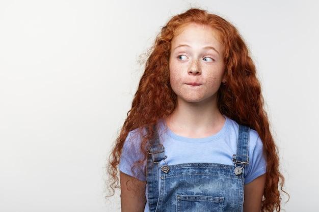 好奇心旺盛なかわいいそばかすの生姜髪の少女の肖像画は、何かを考えて、唇を噛み、左側にコピースペースで白い背景を見ています。 無料写真