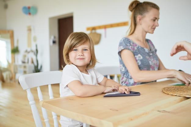 彼女の母親と一緒に木製のダイニングテーブルに座って、幸せな笑顔で折り紙の紙飛行機の作り方を学ぶ白いtシャツのかわいい愛らしい女の赤ちゃんの肖像画。セレクティブフォーカス 無料写真