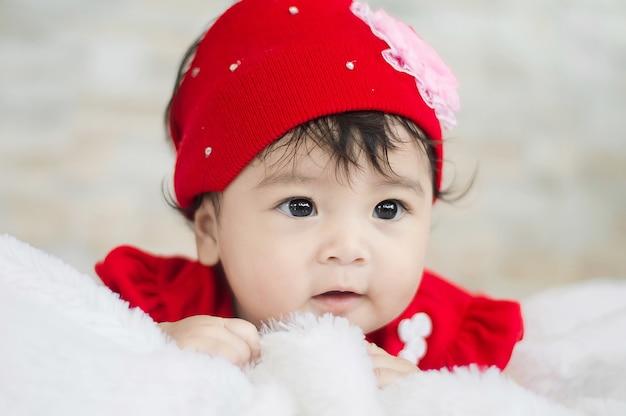 Portrait Of Cute Baby Girl In Red Dress On Blanket Of Fur