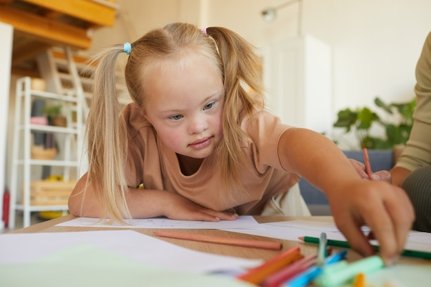 다운 증후군 그리기 및 개발 수업을 즐기면서 연필에 도달 귀여운 금발 소녀의 초상화, 복사 공간 프리미엄 사진