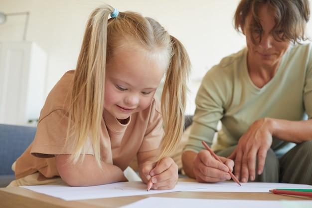 다운 증후군이있는 귀여운 금발 소녀의 초상화는 개발 연습을 즐기면서 어머니 또는 교사와 함께 그리기 프리미엄 사진