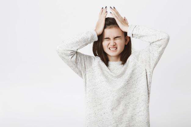 Портрет милой европейской женщины, которая страдает от головной боли, держа руки на имел и сжимает зубы. Бесплатные Фотографии