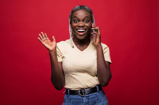 携帯電話で話していると赤い背景に分離された彼女の茶色のロックに触れるトレンディなヘアスタイルでかわいいうれしそうな女性の肖像画 Premium写真