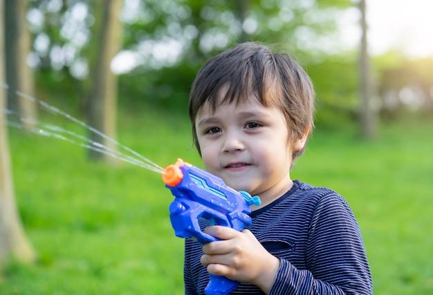 Портрет милый маленький мальчик, играя водяной пистолет в парке | Премиум  Фото