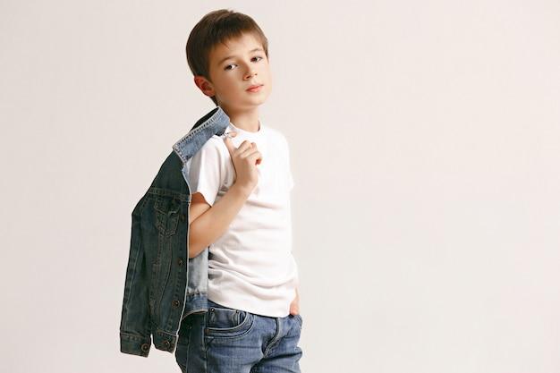 흰색 스튜디오 벽에 카메라를보고 세련 된 청바지 옷에 귀여운 꼬마 소년의 초상화. 키즈 패션 컨셉 무료 사진