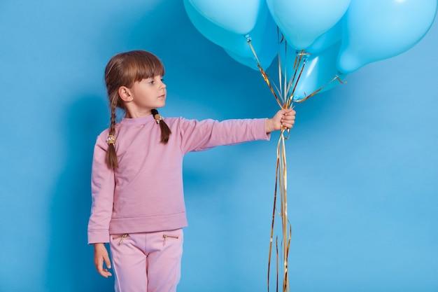 풍선 파란색 벽에 포즈를 취하는 귀여운 미 취학 아동의 초상화 프리미엄 사진
