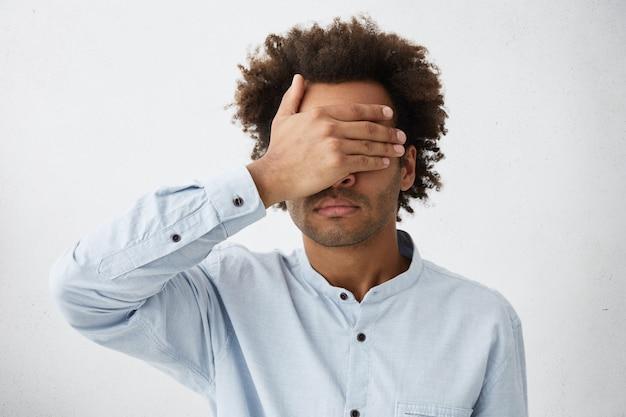彼の顔を覆っている白いtシャツを着てふさふさした髪型の浅黒い肌の混血男の肖像 無料写真