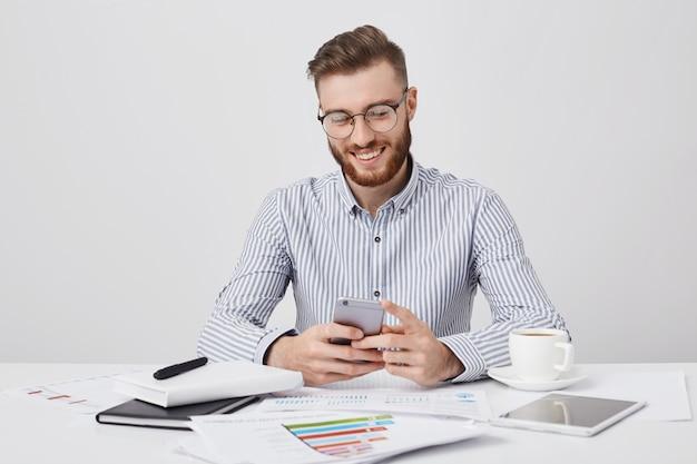 無精ひげとファッショナブルな髪型の楽しい男性の肖像画、ソーシャルネットワークを介してガールフレンドとチャットする様子は幸せそうです。 無料写真