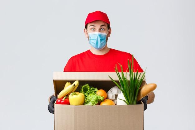 フェイスマスクと食料品の箱の配達人の肖像画 Premium写真