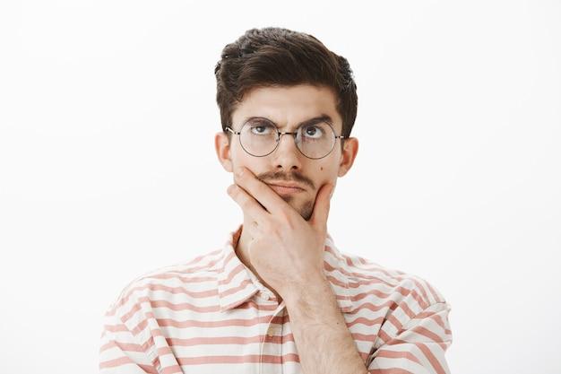 재미있는 콧수염, 턱을 문지르고, 생각하면서 올려다보고, 아이디어 나 개념을 만들고, 어려운 수학 문제를 해결하려고 노력하고, 계산을하는 결정된 집중적이고 창조적 인 남성의 초상화 무료 사진