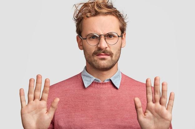 不機嫌そうな表情の不満の若い男の肖像画、一時停止のシンボルを作り、手のひらを前に保ち、否定的な表情をしています 無料写真