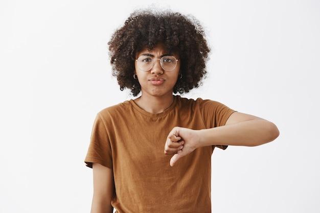 Портрет недовольной и не впечатленной афро-американской симпатичной женщины в очках с афро-прической, показывающей большие пальцы руки вниз и дующейся от разочарования Бесплатные Фотографии
