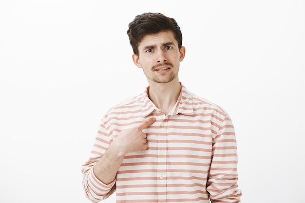 Портрет недовольного привлекательного парня с усами, указывающего на себя указательным пальцем, поднимающего брови от удивления, спорящего, обвиняемого в плохих поступках, разочарованного из-за серой стены Бесплатные Фотографии