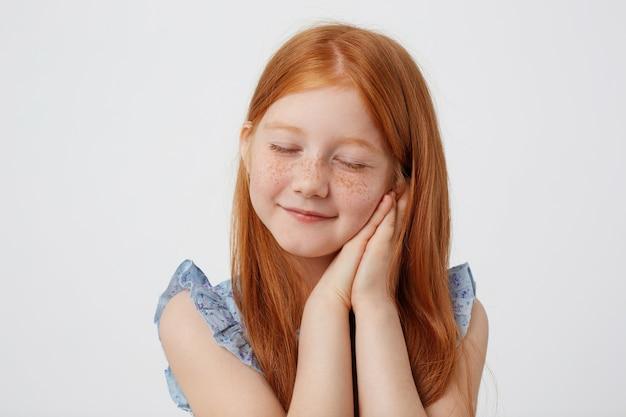 파란 드레스에 작은 주근깨 Red-haired 소녀를 꿈꾸는 초상화, 뺨에 접힌 손바닥으로 조잡 해 보이는 흰색 배경 위에 선다. 무료 사진
