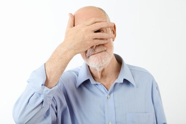 彼の顔に手をつないで、目を覆い、分割された指から覗き見、恥ずかしさを感じて、青いシャツを着た年配の引退した白人男性の肖像画。人間の表情とボディーランゲージ 無料写真