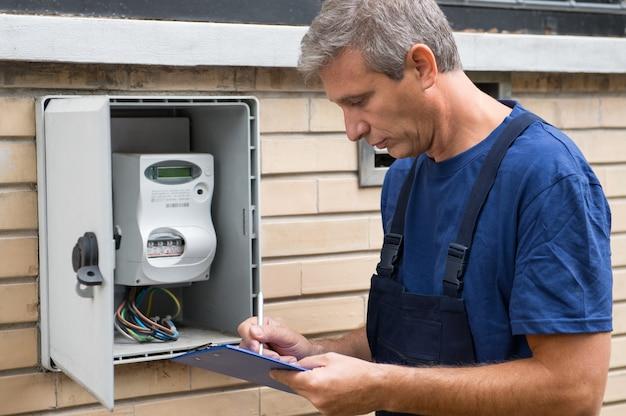 Портрет электрика, проверяющего электрический счетчик Premium Фотографии