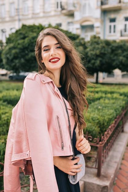 長い巻き毛のポーズでエレガントな少女の肖像画。彼女は黒いドレス、ピンクのジャケット、クラッチバッグ、赤い唇を着ています。彼女は微笑んでいる 。 無料写真