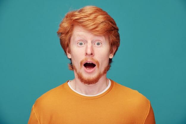 Портрет эмоционального молодого рыжебородого человека, удивленного новостями с открытым ртом на синем Premium Фотографии