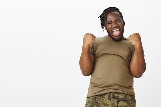 Портрет энергичного парня в коричневой футболке позирует у белой стены Бесплатные Фотографии