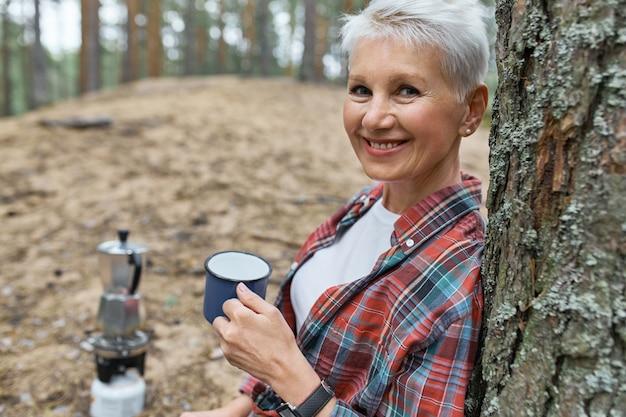 Портрет энергичной пенсионерки, откидывающейся на сосну, держащей чашку, пьющей чай, которую она кипятила в чайнике на походной горелке Бесплатные Фотографии