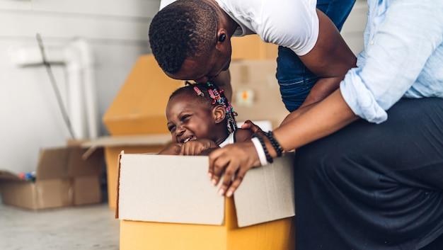 段ボール箱に座って笑って幸せな愛の黒家族アフリカ系アメリカ人の父とアフリカの女の子の笑顔を持つ母を楽しむの肖像画 Premium写真