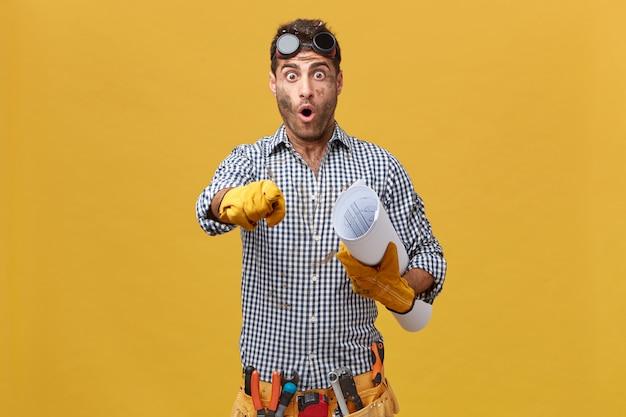 保護眼鏡、市松模様のシャツ、人差し指で指している紙を手に持っている楽器のベルトを身に着けている興奮した男性配管工の肖像画。困惑しているプロの職人 無料写真