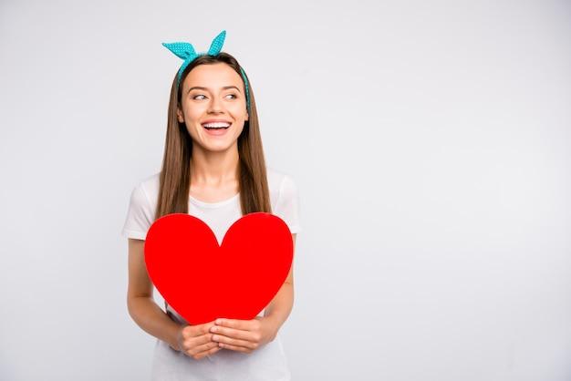 흥분된 긍정적 인 명랑 소녀의 초상화 잡고 빨간 큰 종이 카드 마음 프리미엄 사진