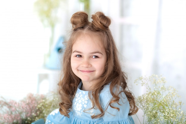 Портрет лица маленькая красивая девушка с длинными волосами. портрет крупного плана маленькой усмехаясь девушки. 8 марта, международный женский день, день матери. портрет счастливой улыбкой ребенка девушка. детство Premium Фотографии