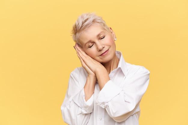 Портрет модной блондинки на пенсии, позирующей изолированной согнутой головой, держащей ладони под щекой и закрытыми глазами, спящей, дремлющей, улыбающейся с удовольствием, имеющей хороший сон Бесплатные Фотографии