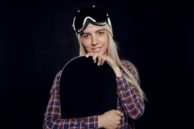 保護ゴーグルと黒いスノーボードを保持している格子縞のシャツを着ているファッショナブルなブロンドの女の子の肖像画 無料写真